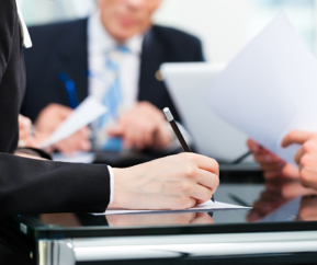 business people at a table holding pen and paper